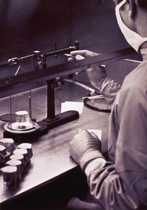 <p>A man is weighing a clear, covered container on a balance scale.  He is pointing to a weight measure mark on the scale with a pencil.  He is wearing a surgical mask on his face.  There are several more containers to be weighed.</p>