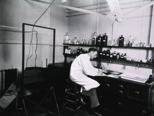 <p>Full length, seated in laboratory, University of Wisconsin.</p>