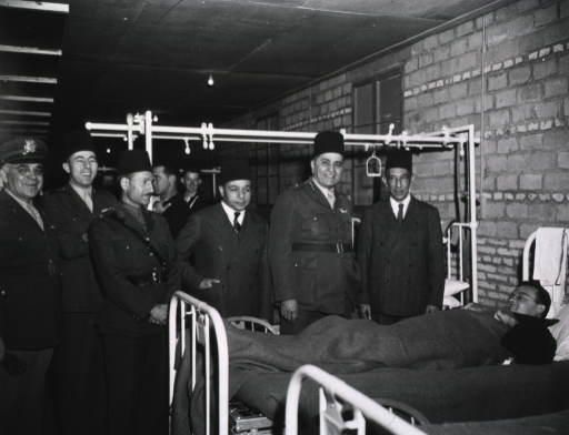 <p>Military personnel, doctors, and dignitaries stand next to a hospital bed on which a wounded soldier lies under a blanket.</p>