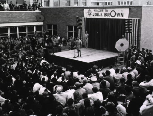 <p>Aerial view of a performance given by Joe E. Brown.  Brown stands at a microphone on a makeshift stage erected in front of the 4th General Hospital building.  A banner welcoming Brown is hung behind him on an outside wall of the hospital.  A crowd is seated around the stage; an orchestra stands to the right of the stage.</p>