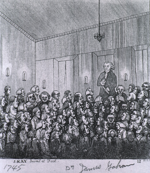 <p>Dr. Graham is standing with a scroll in his hand addressing a large, seated audience.</p>