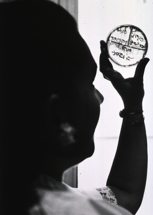 <p>A woman is holding a Petri dish up to the light.</p>