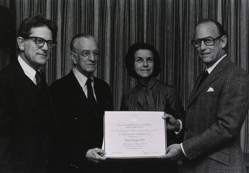 <p>Dr. Martha Vaughan, of the National Heart, Lung, and Blood Institute, is standing between Drs. G. Burroughs Mider and Donald S. Fredrickson, director of the National Institutes of Health.  Drs. Mider and Fredrickson are holding the Mider lectureship award.  Dr. Jack Orloff is standing next to Dr. Mider.</p>