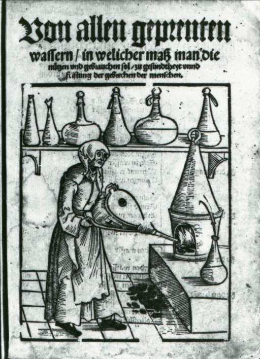 <p>A woman is fanning the flames in a furnace with a hand-held bellows; glassware sits on, and next to, the furnace, as well as on a shelf in the background.</p>