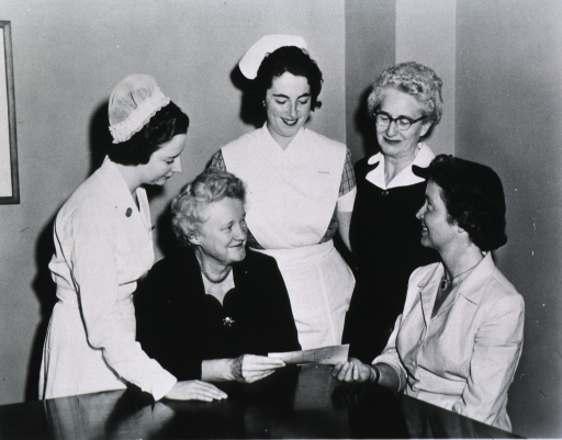 <p>View of members of the organization gathered around a table accepting a check.</p>