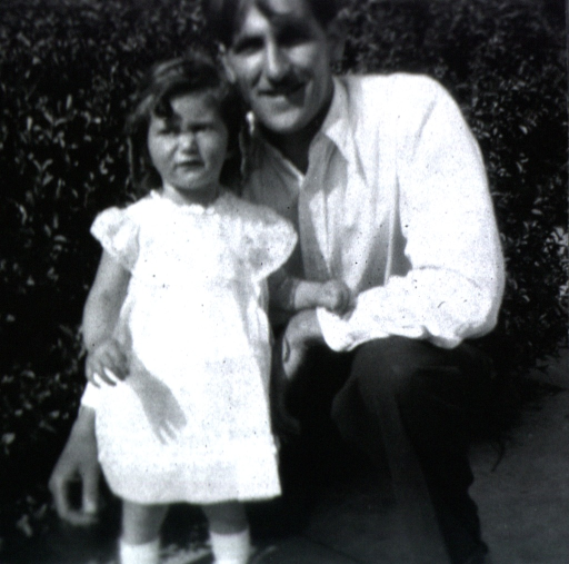 <p>A little girl stands with her father outside near bushes watching the nurse leave.</p>