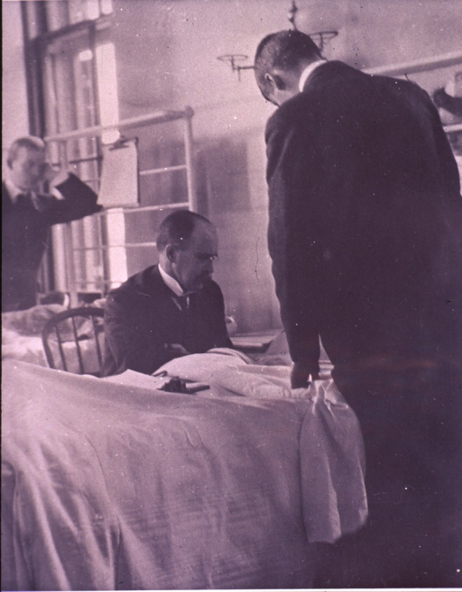 <p>Osler, half-length, is in consultation with a patient; other physicians or students stand nearby.</p>