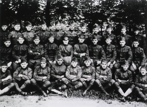 <p>Thirty military personnel in full regalia pose outdoors in three rows:  the bottom row sits on the ground, the middle row sits on chairs, and the top row stands.</p>