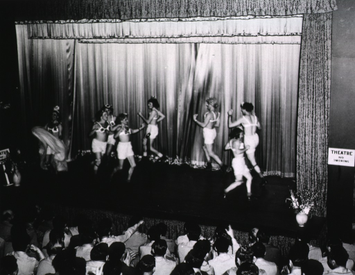 <p>A group of men wearing wigs, bras, and bloomers dances across a stage in a theater in front of an audience of servicemen.</p>