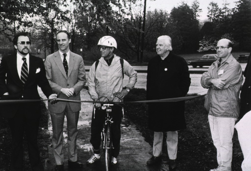 <p>Dr. Fredrickson, director of the National Institutes of Health, is wearing a helmet and standing over his bike.  Montgomery County Executive Charles Gilchrist is standing to Dr. Fredrickson's right and Huly Bray, NIH special events, is to his left.  Also behind the ribbon is an unidentified man.  There is a parking lot and trees behind them.</p>