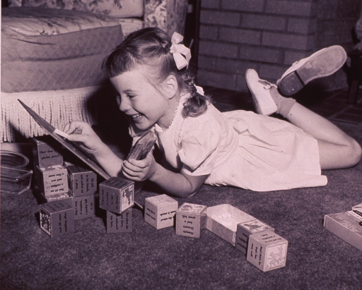 <p>A girl is playing with a chalkboard which is propped up on wooden blocks.</p>