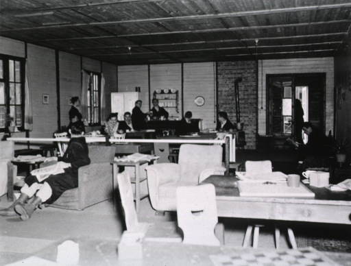 <p>Servicemen sit in chairs or at tables in a room serving as a recreation hall.</p>