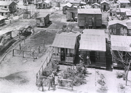 <p>Bird's eye view of a collection of small wooden dwellings with several residents visible in yards and doorways; probably during the New Orleans plague campaign.</p>