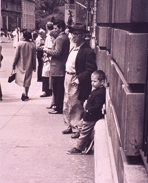 <p>A child is leaning against a building on a busy sidewalk; an old man is standing next to him.</p>