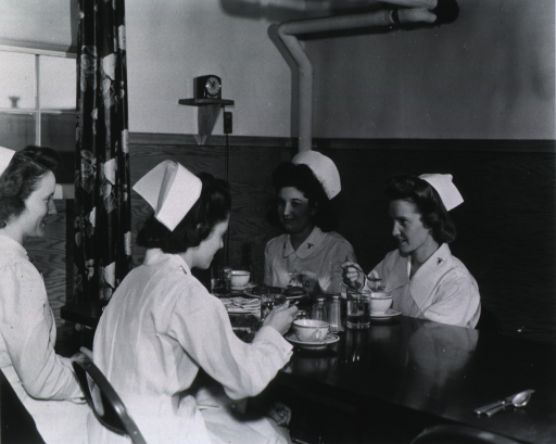 <p>Head and shoulders, left profile, seated in nurses' mess hall with three other nurses.</p>