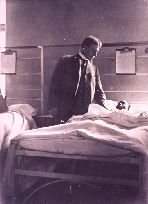 <p>Barker is standing, full length, at the bedside of a black patient.</p>