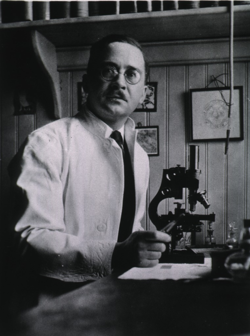 <p>Half-length, full face, at microscope in laboratory, wearing white coat.</p>