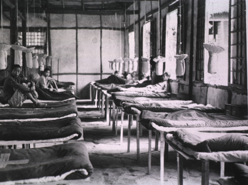 <p>Interior view: two rows of beds with wrapped, circular white material is hanging from the ceiling over the beds.</p>