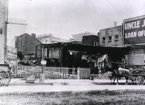 <p>View from across the street of a dilapidated one-story structure, probably condemned for rat-proofing during the New Orleans plague; partially visible sign behind horse on streetfront reads, &quot;Building will be demolished.&quot;</p>