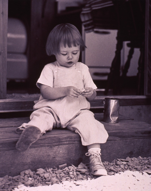 <p>A little girl is sitting on a wooden step; she is examining a stone; there is a can next to her.</p>
