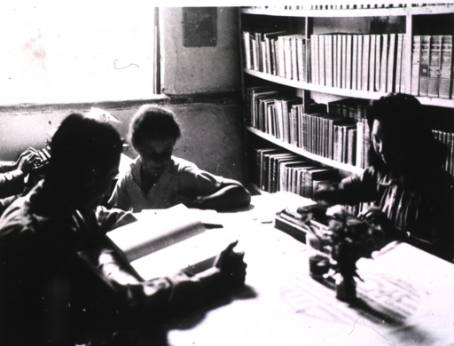<p>Interior view: a man, a woman, and a child are sitting around a table in front of a bookshelf.  In the background someone is typing on a typewriter.</p>