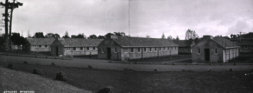 <p>Panoramic view of a row of identical military barracks in an unidentified military base/hospital.  An officer is seen walking toward one of the buildings.  (One of a series of nine photographs by Breckon of the same unidentified military base/hospital.)</p>