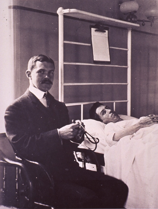 <p>Three-quarter length, right pose, full face, seated in chair at patient's bedside, holding stethoscope.</p>