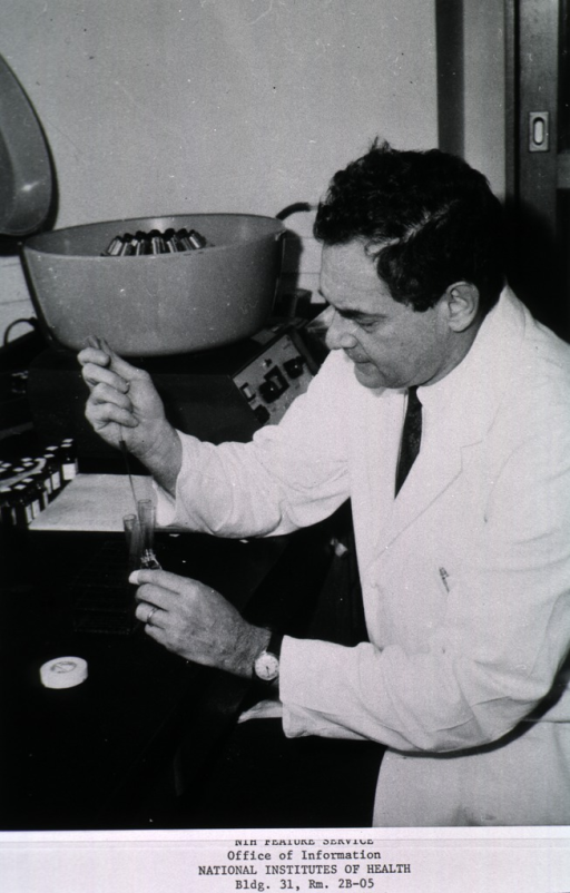 <p>Three-quarter length, left profile, wearing lab coat, seated, working with blood samples (rabbit) in study of genetic problems in transplants, at the University of Illinois Medical Center.</p>