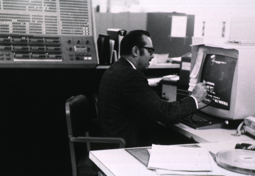 <p>Half-length, right profile, wearing glasses, working at computer.</p>