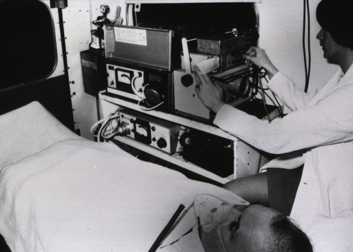 <p>Interior view of an ambulance: a technician is monitoring the vital signs of a coronary patient.</p>