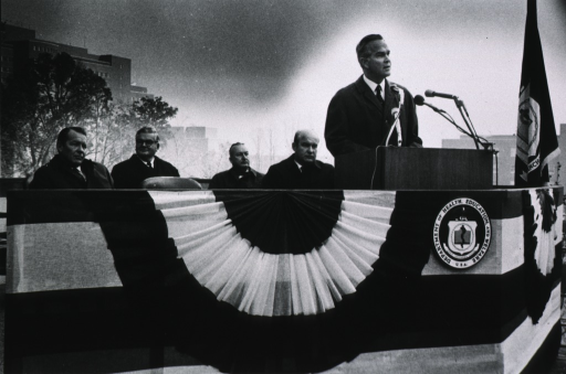 <p>Dr. Robert Marston speaking at the dedication ceremony for Buildings 36 and 37.  Others shown are Robert H. Finch, Dr. Edward F. MacNichol, Jr., Dr. Carl Baker, and Chaplain Leroy G. Kerney.</p>