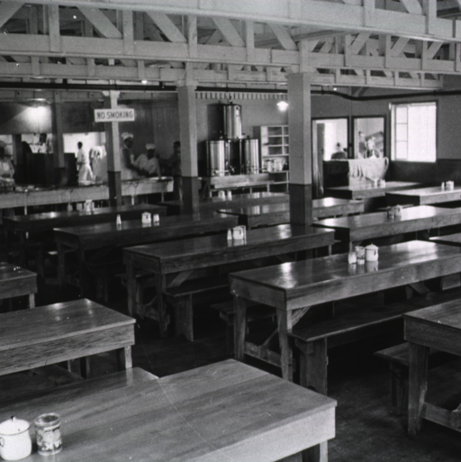 <p>Interior view of an empty military mess hall. On a pillar of which is posted a &quot;no smoking&quot; sign. Cooks and other kitchen staff members stand in the background. (One of a series of nine photographs by Breckon of the same unidentified military base/hospital.)</p>