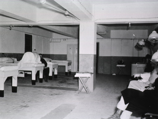 <p>Male patients sit and await therapy.  Across the room, another man sits next to a row of beds.</p>
