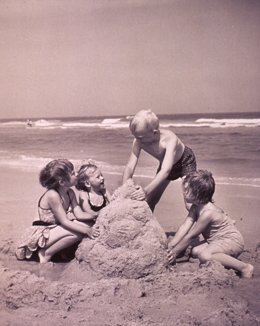 <p>Children are building a sand castle at the beach.</p>