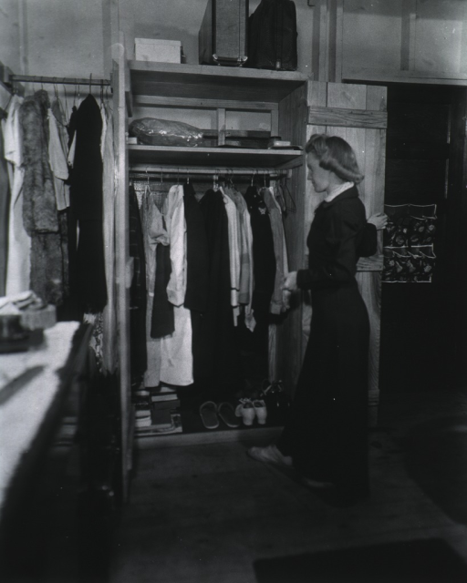<p>Full length, left profile, standing before closet in her quarters.</p>