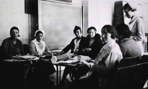 <p>Showing a group of mothers learning to make paper bags, swabs, and cut patterns.  Two student nurses offer assistance.</p>