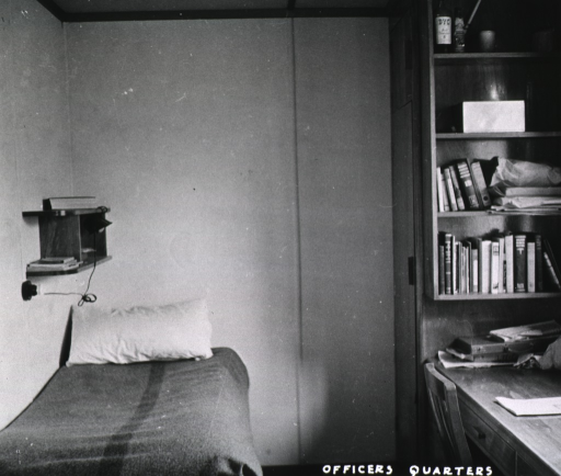 <p>A twin-size bed is positioned in the corner.  Above the  bed is a small bookcase on which a small reading lamp is attached.  A closet/bookcase stands in the opposite corner, along with a desk and chair.  (One of a series of nine photographs by Breckon of the same unidentified military base/hospital.)</p>