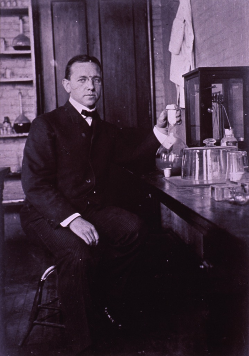 <p>Full length, right pose, full face, sitting at a lab table, holding large flask; wearing glasses.</p>