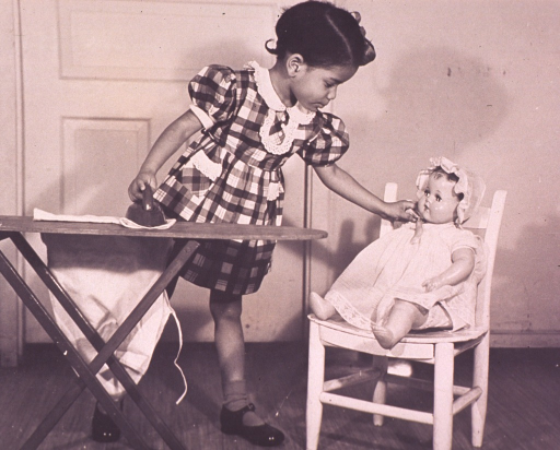 <p>A little girl is play ironing and attending to a doll sitting on a chair next to her ironing board.</p>