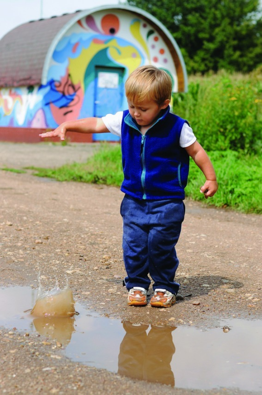 A boy is shown dropping a stone into a puddle. By repeating this predictable activity, he may develop stored representations of the properties of the external world from which accurate predictions of those properties can be formed.