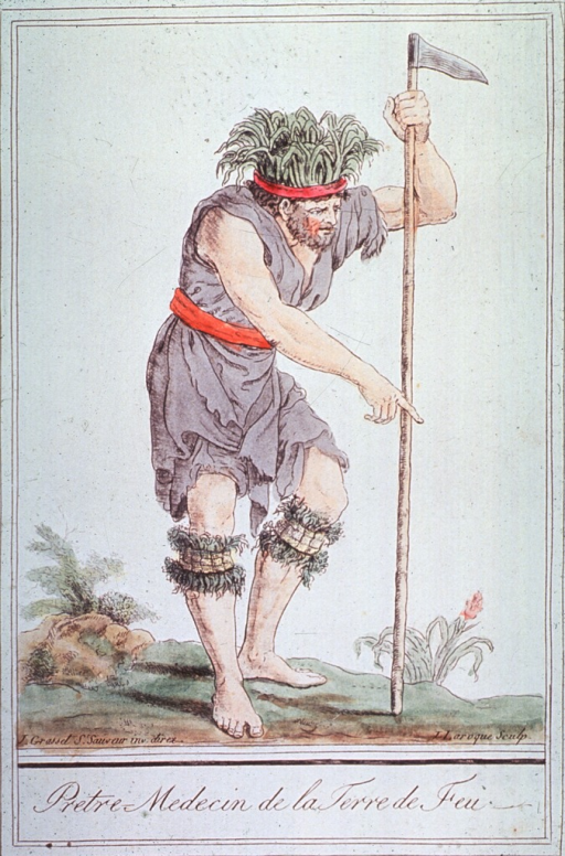 <p>A man standing and holding a long staff with a blade at the top, is wearing the costume of an eighteenth century medicine man from Tierra del Fuego.</p>