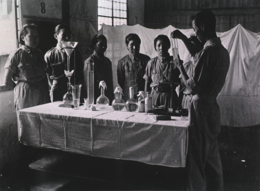 <p>Interior view: People are standing around a cloth covered table on which sit beakers.</p>