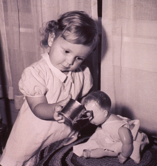 <p>A little girl is giving her doll a drink from a cup.</p>