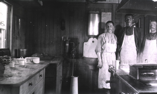<p>Two men stand in a hospital railroad kitchen car.</p>