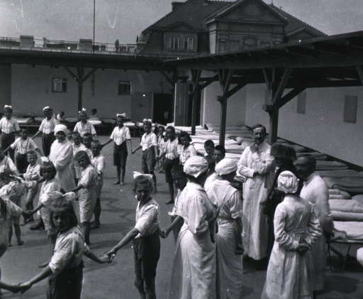 <p>Children and nurses in foreground, others from l. to r. Dr. Pirquet, Mrs. Benedict, Dr. Schick.</p>