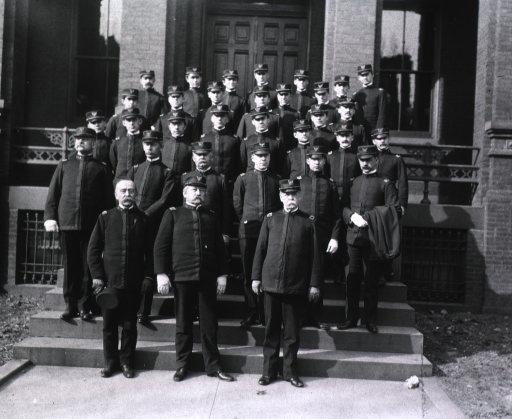 <p>Five rows of servicemen in military uniform pose on the steps in front of the Army Medical Museum.</p>