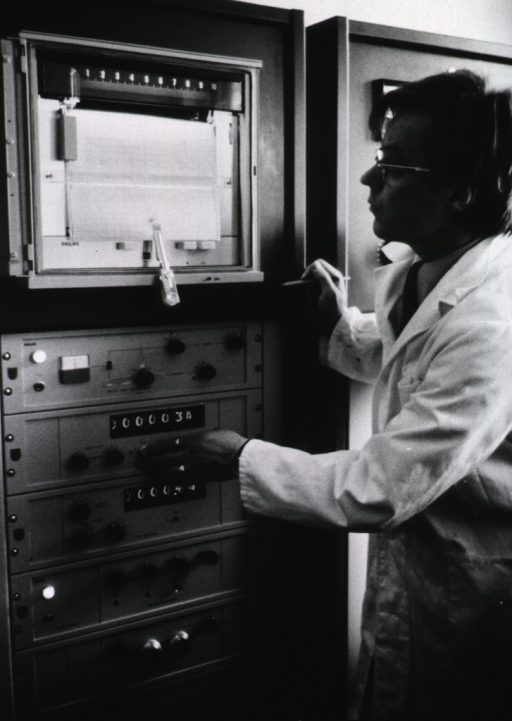 <p>A man is examining the printout from an x-ray emission spectrometer.</p>