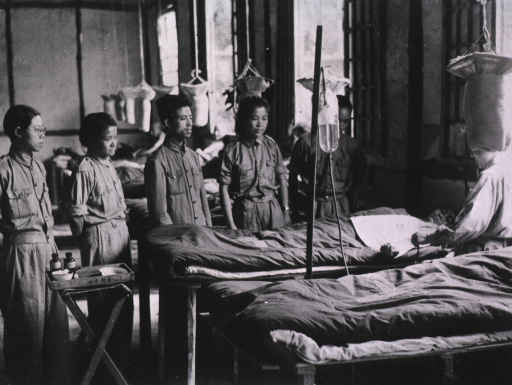 <p>Interior view: students are standing around a bed; a tray is at the foot of the bed; a patient is lying on the bed facing a practitoner.</p>