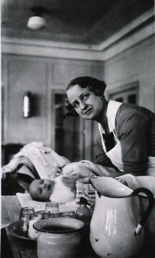 <p>Showing Mrs. Latham bathing an infant.</p>