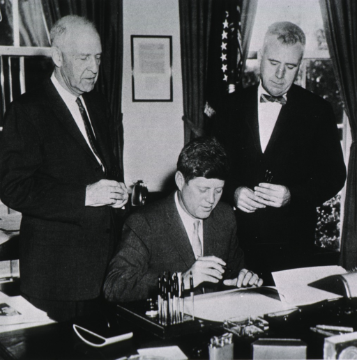 <p>Showing President Kennedy seated at desk; holding pen; Fogarty and Hill are standing behind Kennedy.</p>